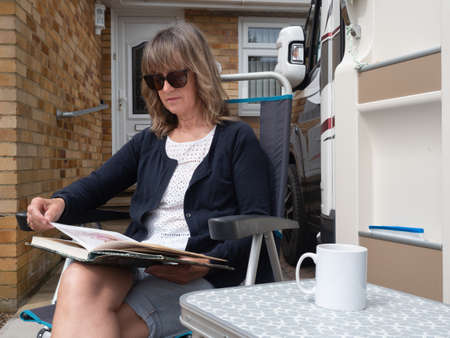 A lady sits outside her house and motorhome reading as she stays at home due to Coronavirus lockdown. A mug is on a table next to her.Recreational Vehicle.Image
