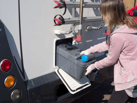 A lady motorhome owner removes a cassette toilet from her motorhome to empty it.She wears gloves.Image