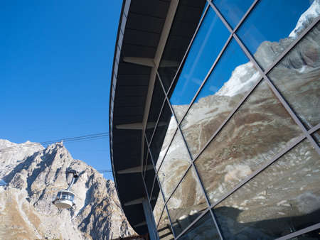 A cable car station on Mont Blanc meaning white mountain shows snow capped mountains reflected in its windows.A cable car can be seen descending on wires with mountains in background