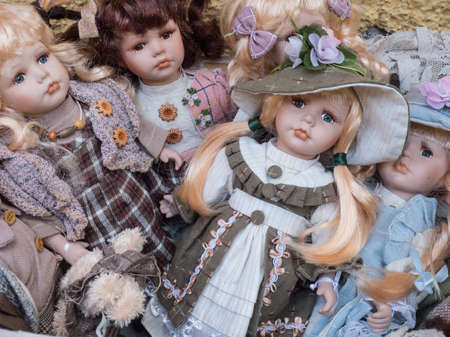 A close view of a group of Bavarian porcelain girl dolls in traditional costume.Some have bows in hair and wear hats