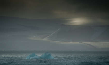 A dramatic arctic landscape with mountains lit by a moody sky and in the foreground an iceberg drifts.Sea Ice