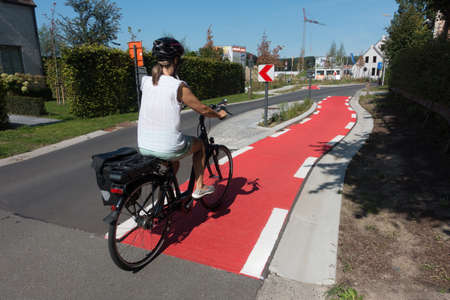A female cyclist cycles on a dedicated cyle lane which is painted red and runs next to a road.She wears a cycle helmet and has a pannier on her bike