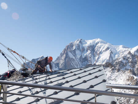 A climber in full safety gear climbs over the edge of a rooftop to make repairs with dramatic backdrop of Mont Blanc in the background Reklamní fotografie