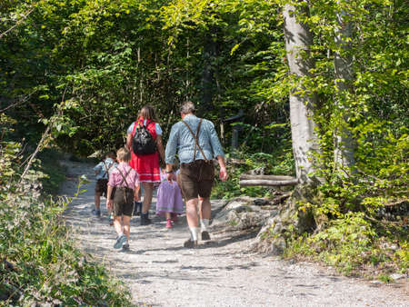 A family dressed in traditional german alpine shorts and checked  shirts and dresses walk along a path in a mountain woodland