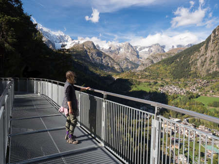A female walker stands on a high metal walkway looking at a dramatic view over a valley towards the Mont Blanc mountain range.Italy