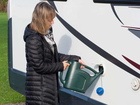 A lady is refilling the drinking water tank of her motorhome using a green watering can.The blue filler cap hangs down as the fresh water is poured into the side of the recreational vehicle