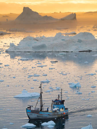 A Greenland fishing boat moves through melting sea ice with drifting icebergs in background lit by orange glow of sunset.Climate Crisis.Vertical Image