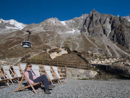 A female walker wearing sunglasses relaxes on a deck chair with a dramatic mountain range in background and a cable car in view.Sunny day and blue sky.Mont Blanc (white mountain).Italy