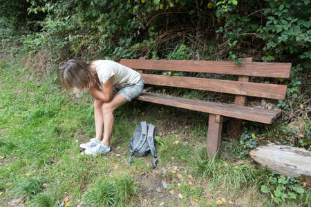 A female walker sits on a wooden bench with her head in her hands and elbows resting on her knees looking tired out. A ruck sack lies on the grass at her feet.
