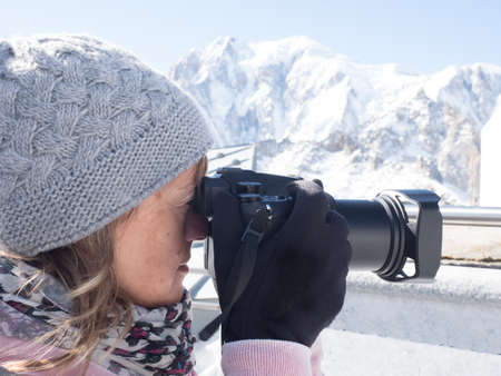 A lady photographer takes a photograph wih a winter snowy mountain background.She wears knitted woolen hat gloves and a scarf.