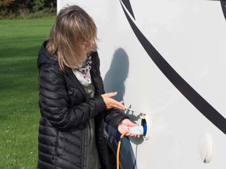 A lady lifts a cover flap and plugs in an orange electric hook up lead into the side of her motorhome to provide power to the camper van.Recreational Vehicle