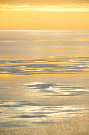 A golden sunset casts an orange glow over tranquil silvered sea