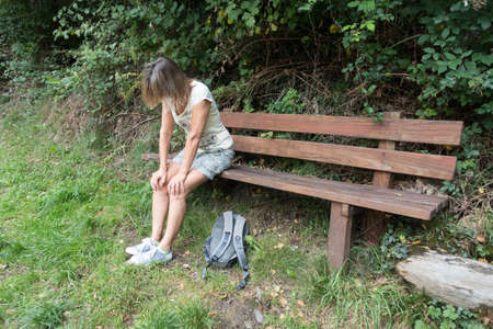 A female walker sits on a wooden bench with hands on her knees looking tired out. A ruck sack lies on the grass at her feet