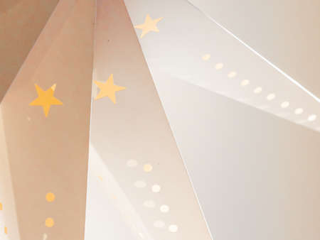 A home made paper Christmas decoration in white with cut out stars and circles with orange and white light Reklamní fotografie