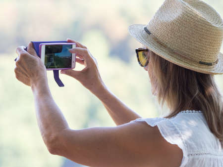 A lady traveller wearing a straw hat and sunglasses takes a landscape photograph with her smart phone. Her arms are outstretched as she composes the shot