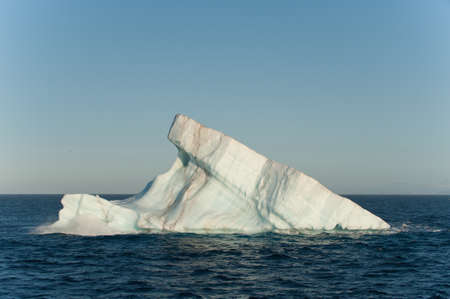 A large iceberg drifts at sea in Arctic Ocean having detached from a glacier.Copy Space above.Climate Crisis Reklamní fotografie