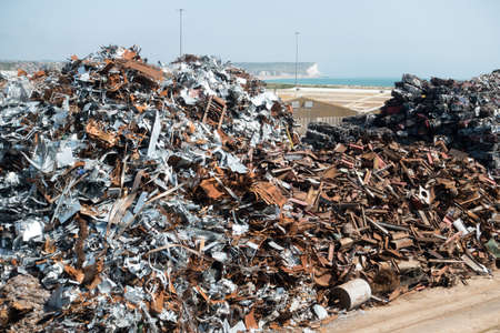 A large pile of scrap metal awaits shipment on a dock side jetty. White cliffs of West Sussex are visible on distant horizon Banque d'images