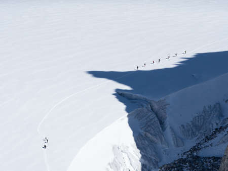 A line of walkers look tiny in contrast to a large glacier which they walk on.Shadows of a mountains peaks are cast onto their route