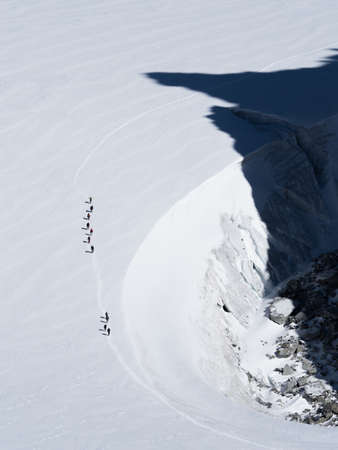 A line of walkers look tiny in contrast to a large glacier which they walk on.Shadows of a mountains peaks are cast onto their route.Vertical Image Reklamní fotografie