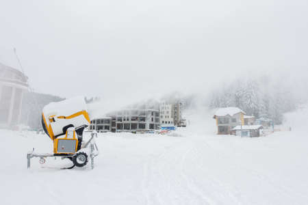 A mobile snow making machine on ski slope pumps out snow.In the background are buildings which are barely visible due to spray from the machine.Industrial.