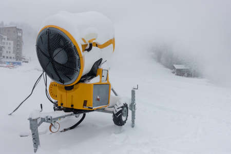 A mobile snow making machine on ski slope pumps out snow.In the background are buildings which are barely visible due to spray from the machine.Industrial