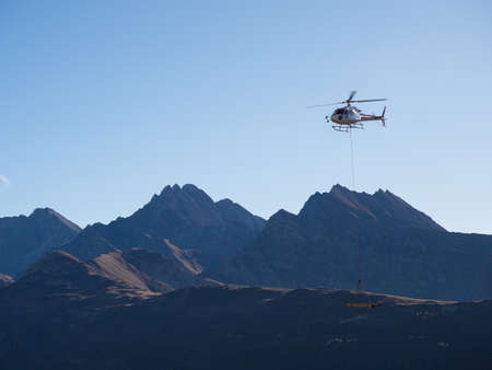 A mountain scene with a helicopter flying and transporting materials that hang from a cable attached to the helicopter.