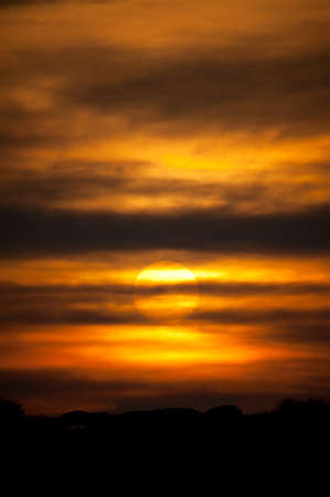 A setting sun behind layers of cloud and deep orange sky tones with a black horizon.Vertical Image Reklamní fotografie