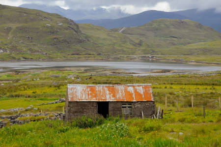 A traditional crofters stone built store with a rusting corrugated roof.An inland loch and mountains are in the background. Reklamní fotografie