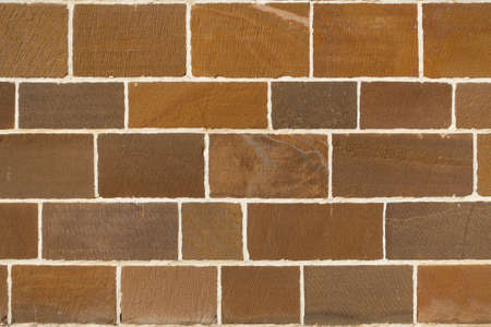 A wall with different shades of brown brickwork with cream coloured mortar lines joining them.Architecture