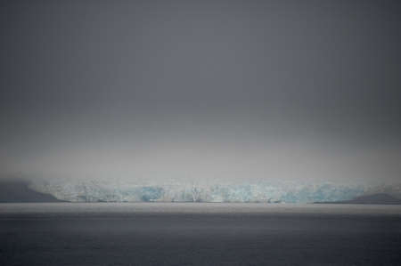 A view across a dark arctic sea with a glacial wall with lue ice in the distance reaching the ocean.Above a darkening sky creates an atmospheric image of climate change.Climate emergency