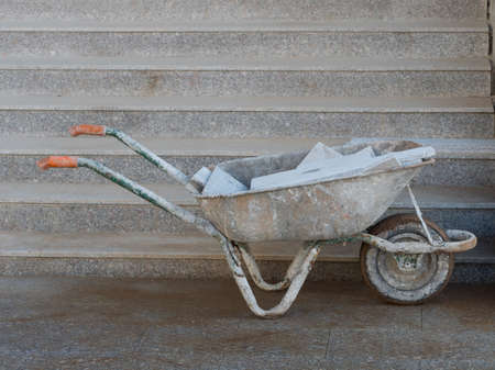 A wheelbarrow covered in grey stone dust contains grey stone tiles and stands in front of grey steps.It has orange contrasting handles
