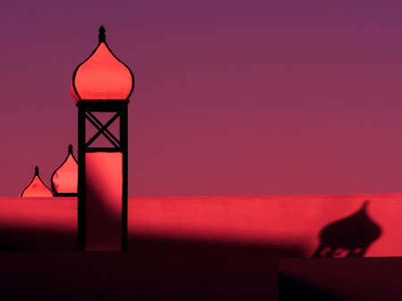 Roof top architecture with onion domes are lit by a red sunset light and dramatic shadows are cast