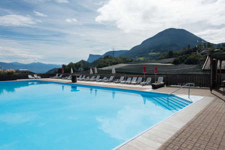 A clear still blue swimming pool is set amongst Italian mountains in a campsite with mountains . Italy.