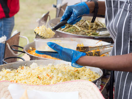 A store holder at a festival dishes up food into a plastic container wearing blue gloves and an apron to avoid cross infection. Arms and hands can be seen with pans of rice carrot and greens visible Reklamní fotografie