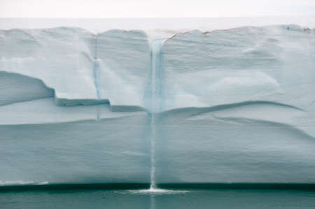 Melting ice water falls from a glacial wall as a waterfall into a turquoise ocean.Climate Change.Climate Emergency and Breakdown Reklamní fotografie