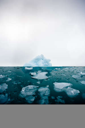 A wide low angle view of melting sea ice floes in still waters of Northern Arctic with iceberg in Portrait format.Climate Crisis and Breakdown.Climate emergency.