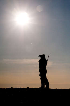 Wildlife guide with rifle silhouetted against a blazing sun