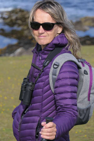 A female bird watcher in a purple down jacket with binoculars,rucksack and sunglasses smiles towards camera.Her hand is seen resting on a walking pole Reklamní fotografie