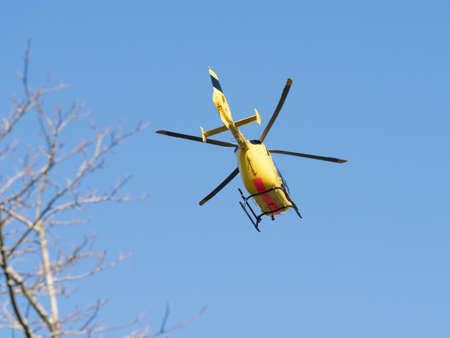 A yellow helicopter against blue sky Foto de archivo