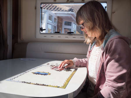 A lady looks at a jigsaw puzzle she is completing in her motorhome recreational vehicle