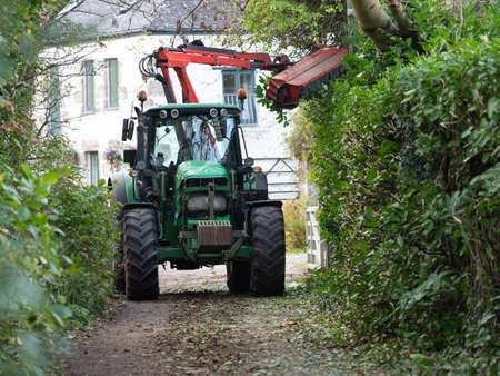 A tractor with special attachment cuts a hedgerow in a country lane