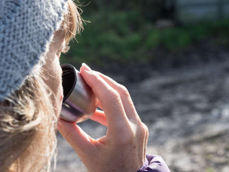 Close up of a lady wearing a bobble hat with focus on her drinking from a silver cup of a flask