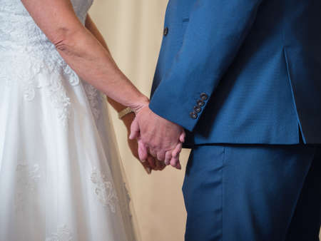 Closeup of married couple holding both hands at a wedding ceremony.The bride and groom are facing each other.