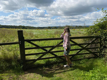 A lady in a pink hoody wearing shorts leans side on to a wooden farm gate looking out towards a wild meadow. looking thoughtful with head on her arm.Sunny day with blue sky and white clouds Reklamní fotografie