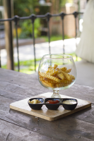 french fries plate: French fries in the glass bowl on the wooden table