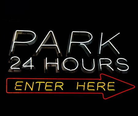 neon car park sign isolated on black photo