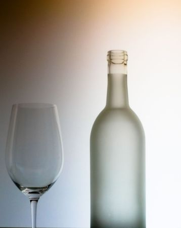 frosted glass wine bottle and a single glass