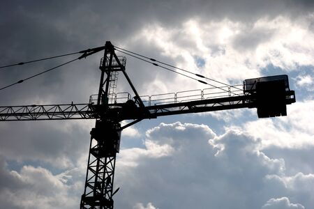 Tower crane in the mountains under storm clouds