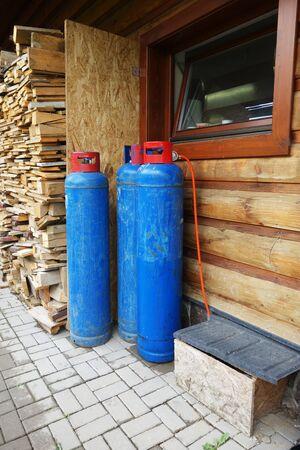 Gas bomb behind a wooden cottage for cooking in the kitchen