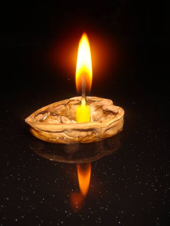 Floating candle burning on a nut shell Stock Photo